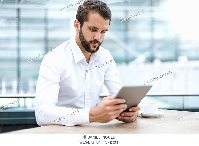 Young businessman using tablet in a cafe