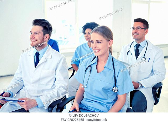 profession, medical education, health care, people and medicine concept - group of happy doctors on seminar in lecture hall at hospital