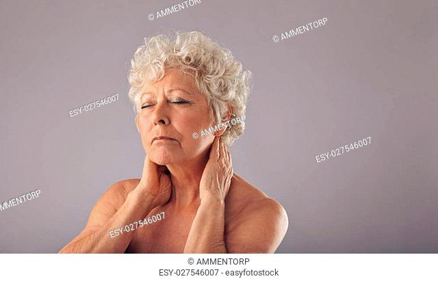 Portrait of mature woman holding her neck in discomfort against grey background. Shirtless senior woman with neck pain