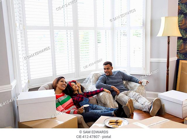 Family taking a break from packing, moving house