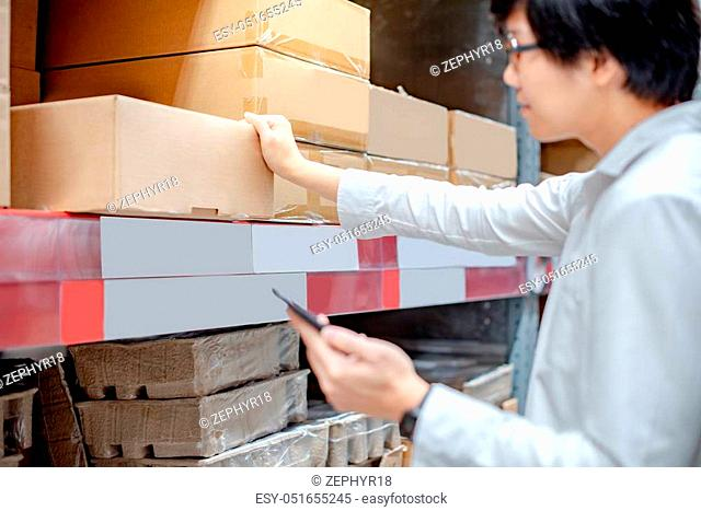 Young Asian man checking the shopping list on his smartphone at product shelves. Warehouse shopping lifestyle concept