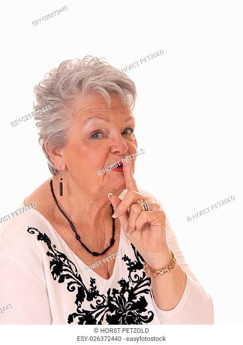 A pretty senior woman with short gray hair in a closeup picture holding.one finger over her mouth, isolated for white background.