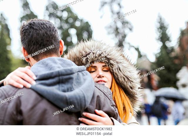 Portrait of young woman with eyes closed hugging her boyfriend outdoors