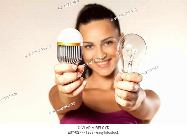 young smiling girl holds in her hands the old and the new generation of light bulbs