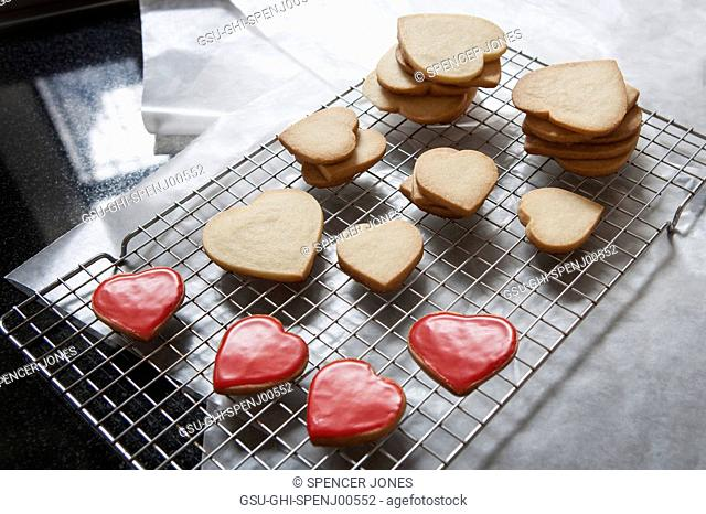Small and Large Heart-Shaped Shortbread Cookies on Cooling Rack, Some with Red Glaze