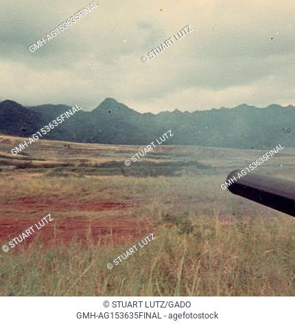 Tip of the barrel of an artillery canon is visible firing into a field in Vietnam during the Vietnam War, 1968. ()