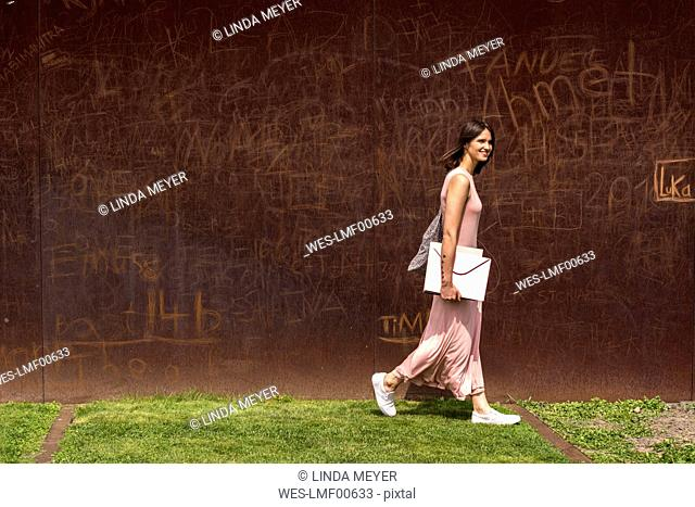 Smiling young woman walking in front of corten wall