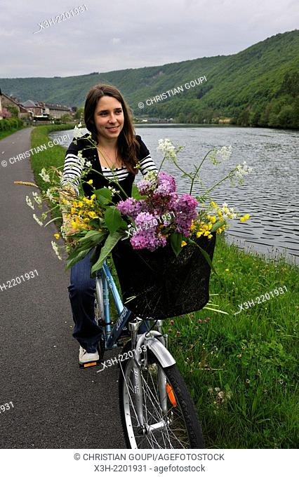 young woman cycling on cycle lane along the Meuse River at Haybes, Ardennes department, Champagne-Ardenne region of northeasthern France, Europe