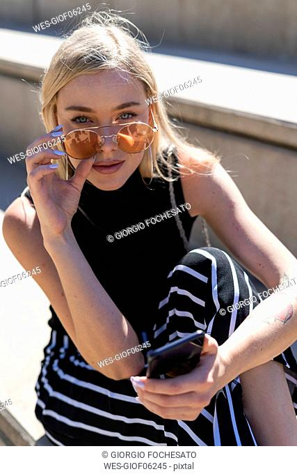 Portrait of fashionable young woman sitting on stairs outdoors wearing sunglasses