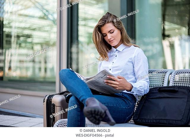 Portrait of young businesswoman with baggage sitting on bench reading newspaper