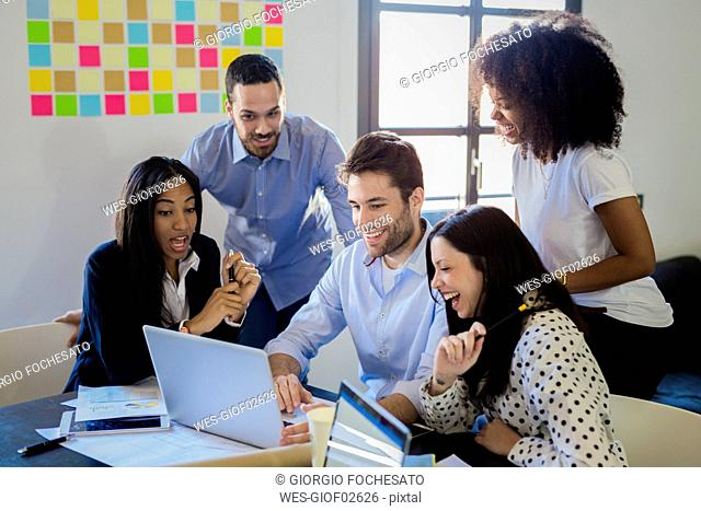 Happy business people in office sharing laptop