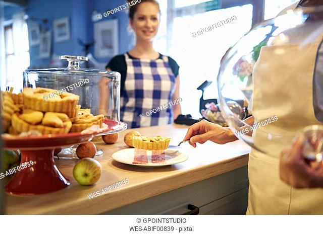 Woman working in a cafe serving a piece of cake