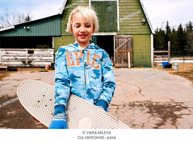 Blond boy carrying skateboard in farmyard, portrait