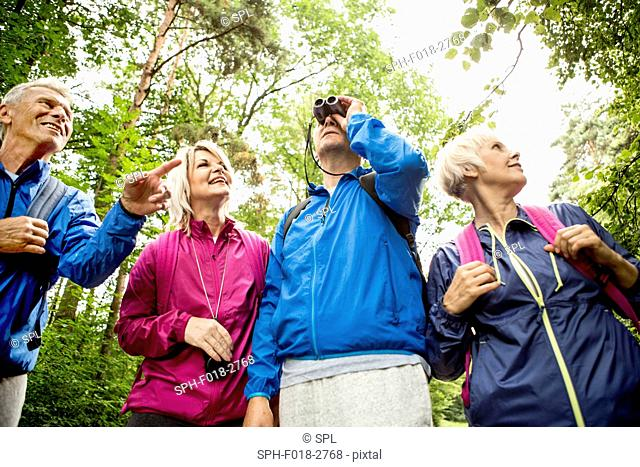 MODEL RELEASED. Four people on hike with binoculars
