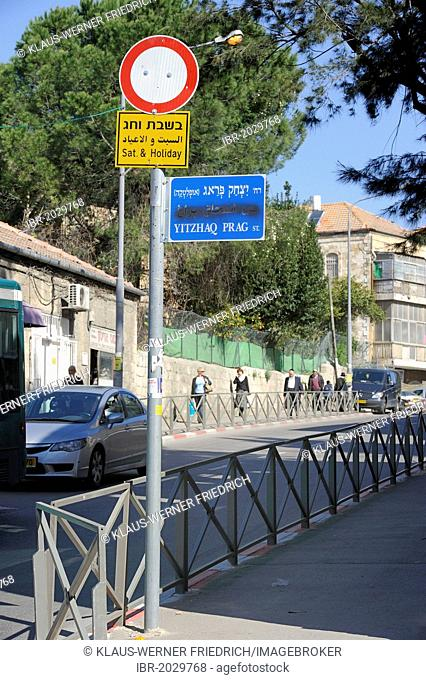 Street name sign with the Arabic name sprayed over, Orthodox Jews at the rear, Jerusalem, Israel, Middle East