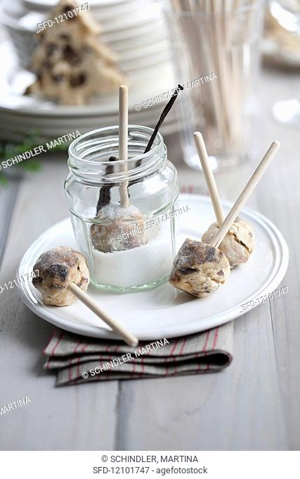 Stollen balls on wooden skewers being covered in rosemary and vanilla sugar