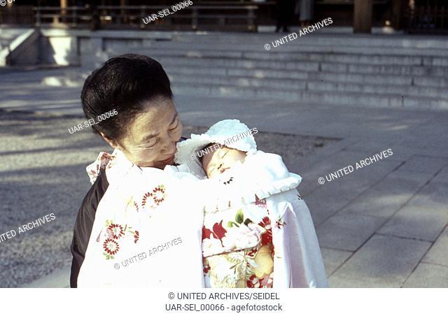 Die Großmutter bringt einen Täuflimng zum Meiji-Schrein im Stadtbezirk Shibuya in Tokio, Japan 1960er Jahre. Grandmother bringing a child to be baptised to...