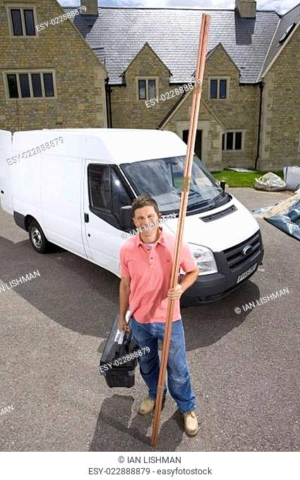 Smiling male plumber holding toolbox and copper pipes near work van
