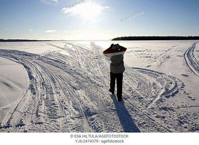 man walking toward sun on frozen lake, Finland