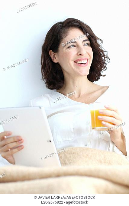 Woman using digital tablet and holding a glass of juice