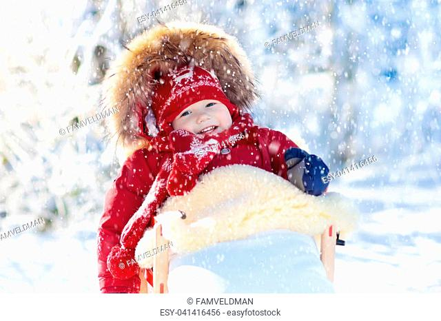 Sled and snow fun for kids. Baby sledding in snowy winter park. Little boy in warm red jacket and knitted hat sitting in sheepskin footmuff