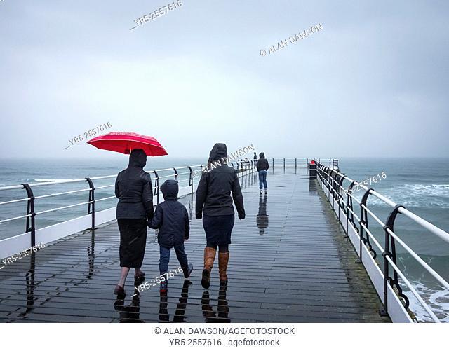 People walking on Saltburn`s Victorian pier in the rain. Saltburn by the sea, North Yorkshire, England, United Kingdom