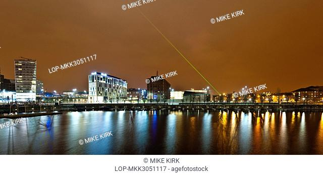 England, Merseyside, Liverpool. Liverpool One shopping centre with green laser in the night sky and reflections in the waters of Salthouse Dock