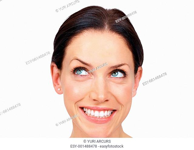 Closeup of lovely young woman in cheerful mood smiling over white background, looking away