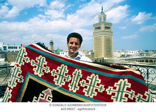 Carpet seller. Souq. Zitouna mosque at the back (XVIIth century). Tunis. Tunisia