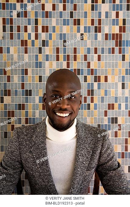 African man in tweed jacket smiling in front of tiled wall