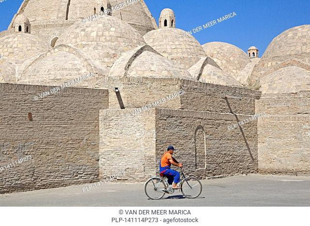 Uzbek man cycling in front of mosque in the ancient historic city of Bukhara / Buxoro, Uzbekistan