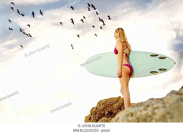 Caucasian woman standing on rock holding surfboard