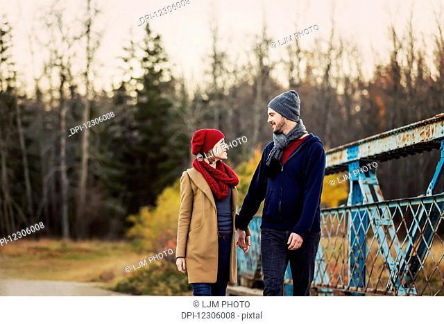 A young couple walking on a bridge in a city park in autumn; Edmonton, Alberta, Canada
