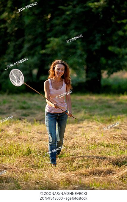 girl with a butterfly net looking for insects