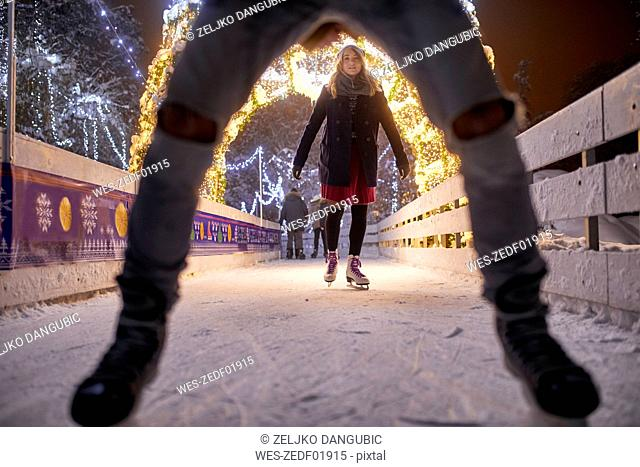 Young woman ice skating on an ice rink at night
