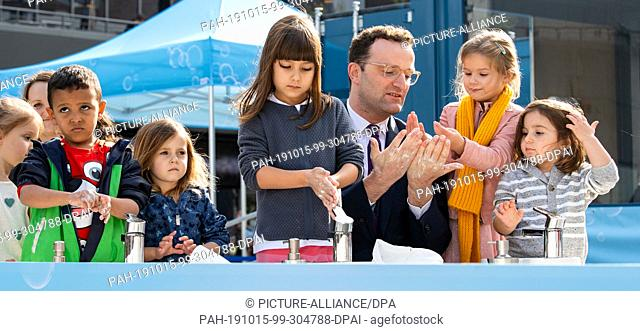 15 October 2019, International, Berlin: Jens Spahn (CDU), Federal Minister of Health, washes his hands together with children from a Berlin kindergarten on the...