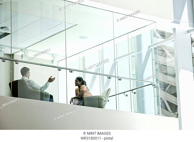 Businessman and woman standing behind a conference room window in large business centre