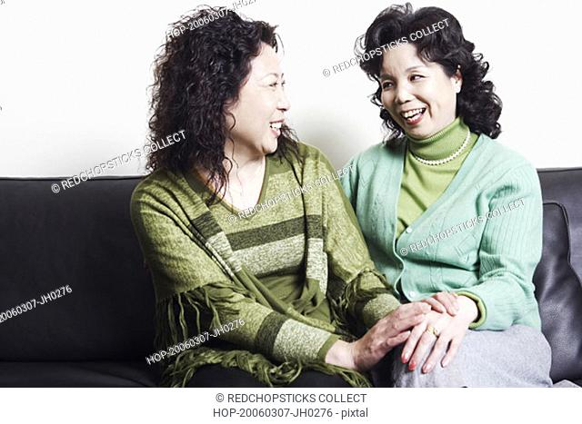 Close-up of two mature women looking at each other smiling