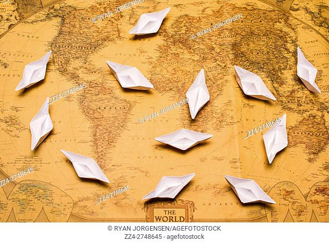 Overhead view of twelve little folded paper boats scattered about on old yellow world map. Nautical adventures