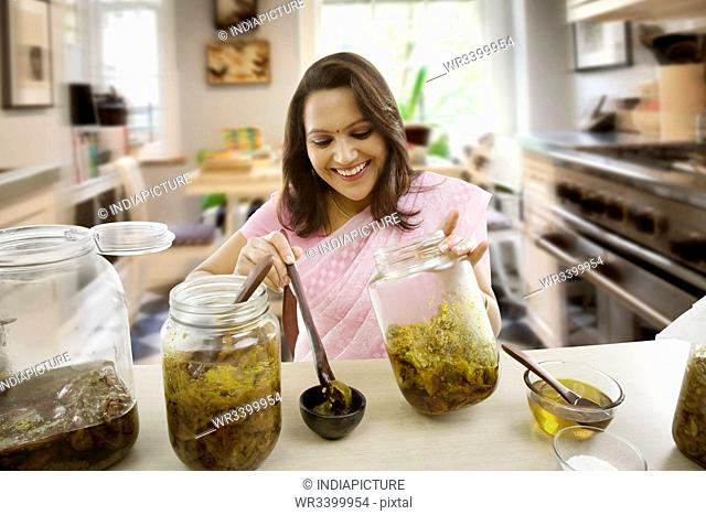Woman putting pickle into a bowl