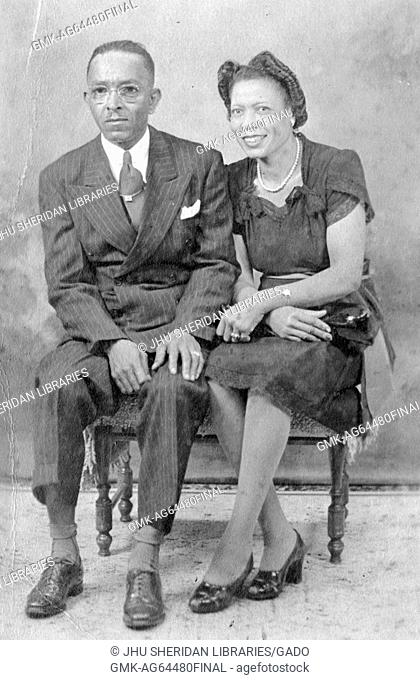 Portrait of African-American couple wearing suit and formal dress, in photographic studio, 1930