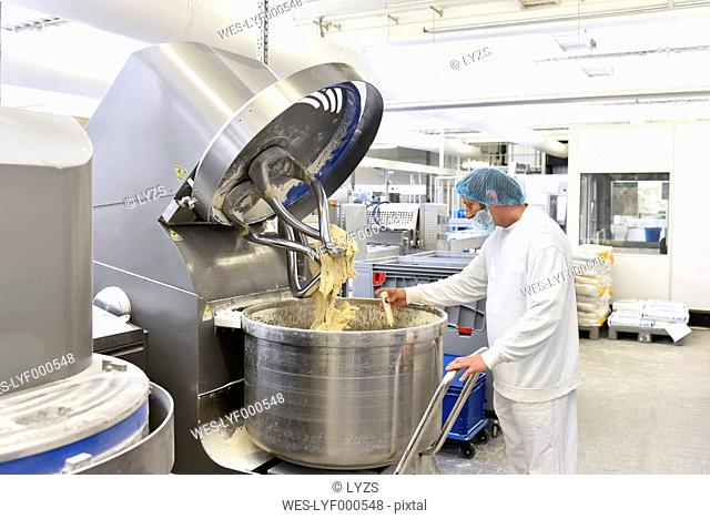 Worker at dough kneading machine in an industrial bakery