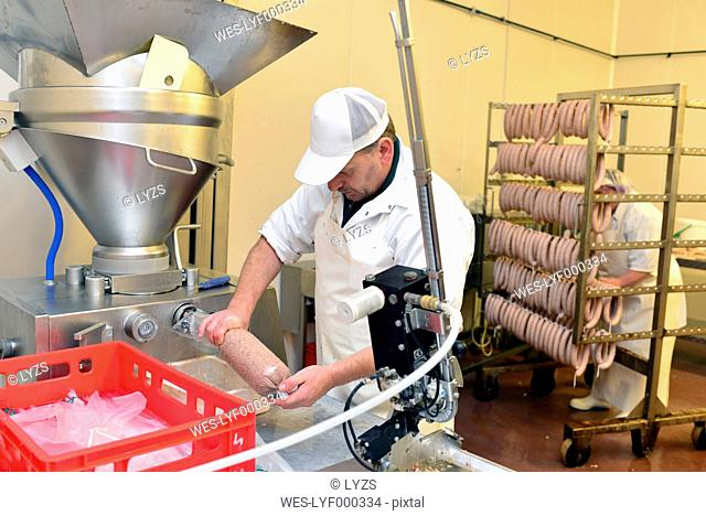 Man working at sausage production in a butchery