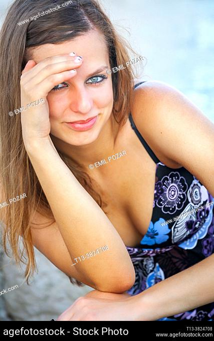 Attractive teenager girl is smiling at camera shading eyes against excessive sunlight