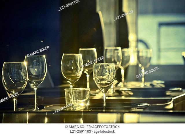 Cups, plates and cutlery on a table at sunset