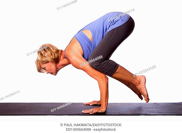 Beautiful woman standing on hands with feet lifted up doing Crane Bakasana yoga pose, on white