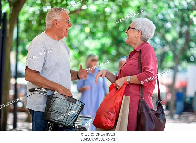 Senior man and mature woman chatting in city