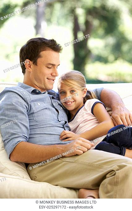Father And Daughter Sitting On Sofa At Home