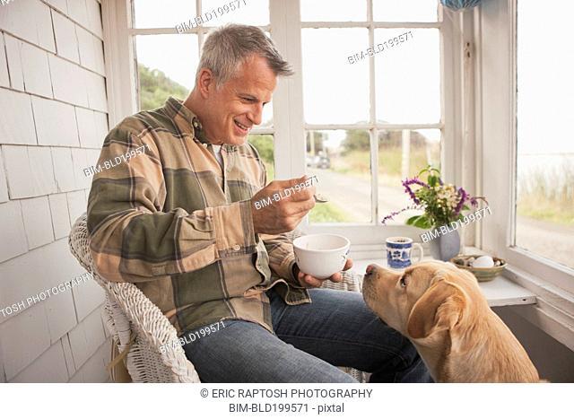 Dog watching Caucasian man eating breakfast