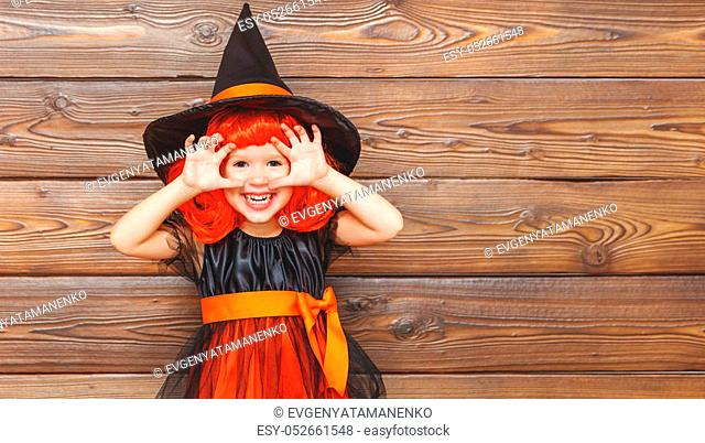 funny child girl in witch costume for Halloween scares on a dark wooden background